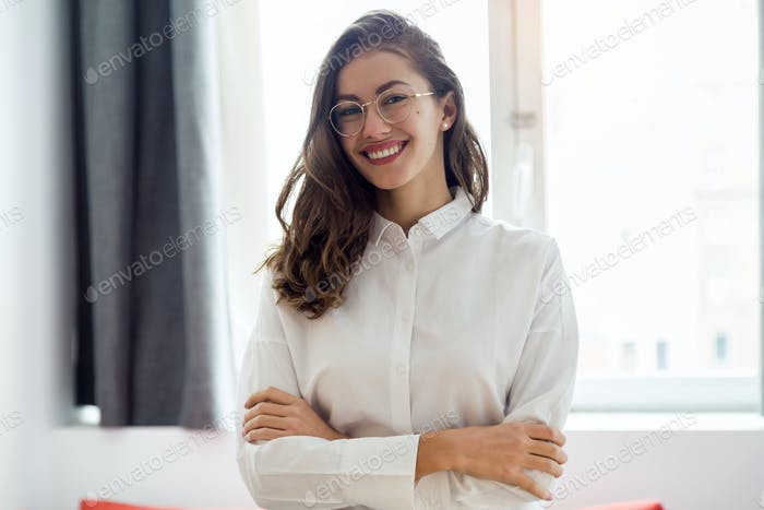 Beautiful smiling businesswoman with eyeglasses looking at the c