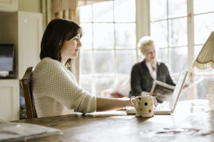 Zwei Frauen zu Hause sitzen an einem Küchentisch, Mutter und Tochter