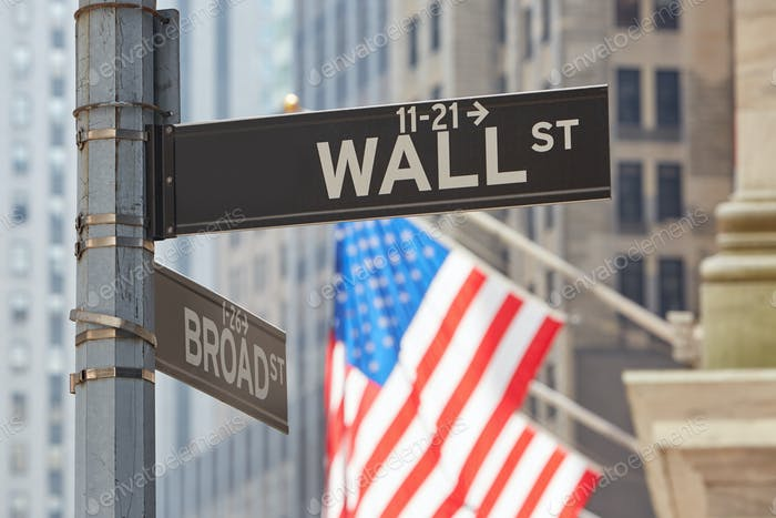 Wall Street sign near Stock Exchange with US flags, New York
