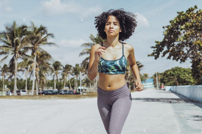 Black fit girl jogging on tropical waterfront