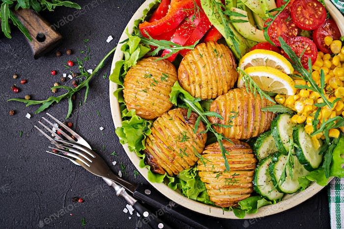 Vegetarian buddha bowl. Raw vegetables and baked potatoes in  bowl