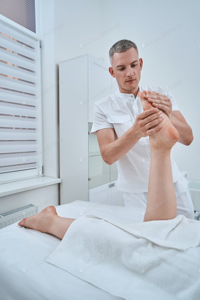Experienced concentrated physiotherapist using an acupressure massage