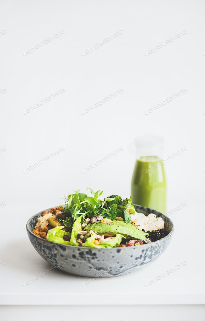 Healthy vegan superbowl with vegetables and green smoothie, copy space