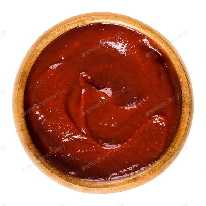 Tomato ketchup in wooden bowl over white