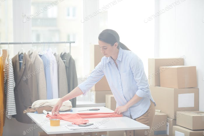 Young office manager of online shop preparing casualwear for one of clients
