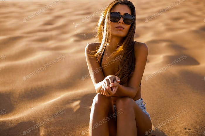 Young girl sitting on a sand dune