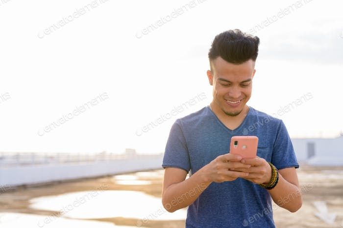 Happy young handsome multi ethnic man using phone at rooftop of the building