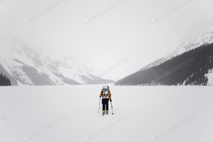 A skier ,a frozen lake on the Wapta Traverse,a mountain hut-to-hut ski tour in Alberta,Canada.