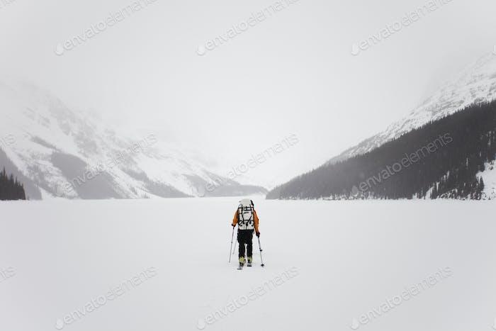 Ein Skifahrer, ein gefrorener See auf der Wapta Traverse, eine Berghütte Skitour in Alberta, Kanada.