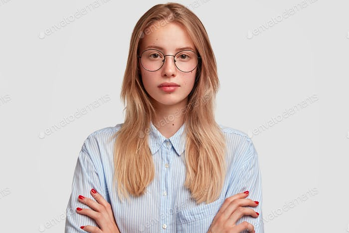 Studio shot of beautiful female youngster looks seriously at camera, listens attentively somebody, k