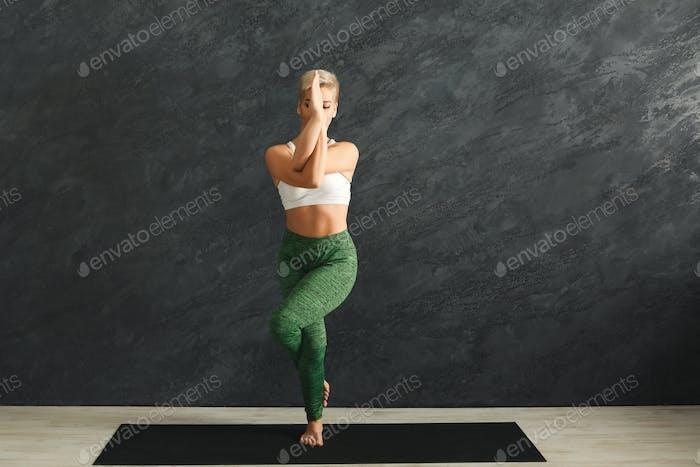 Woman training yoga in eagle pose