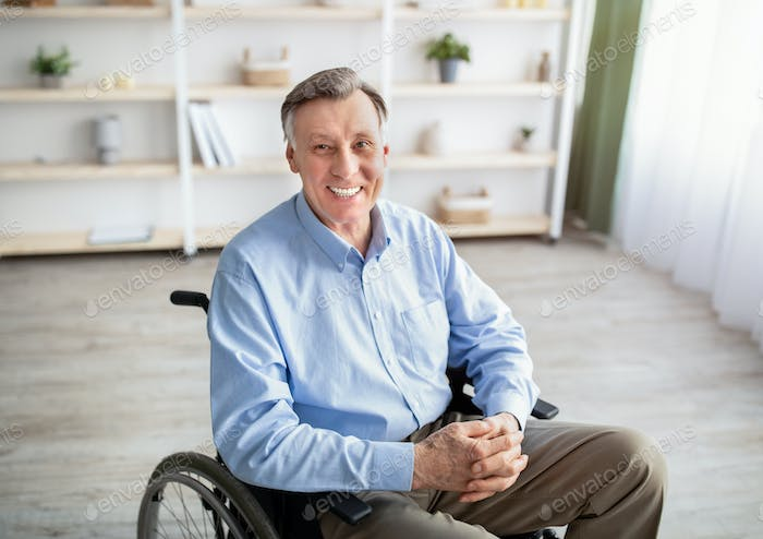 Portrait of joyful impaired senior man in wheelchair posing and smiling at home