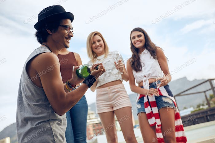 Man opening a bottle of champagne at party