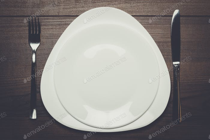 white plates with knife and fork on wooden table