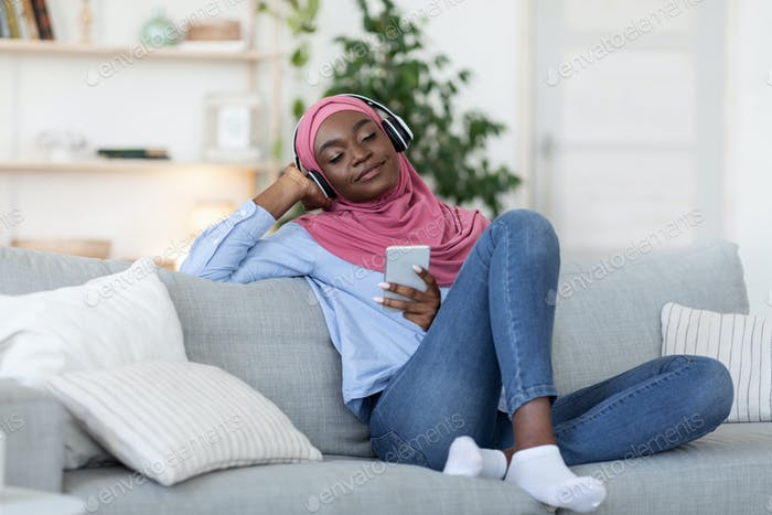 Playlist For Relax. Black Islamic Woman Listening Music On Smartphone At Home