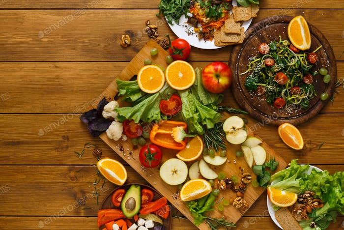 Wooden table served with cut fruits and vegetables