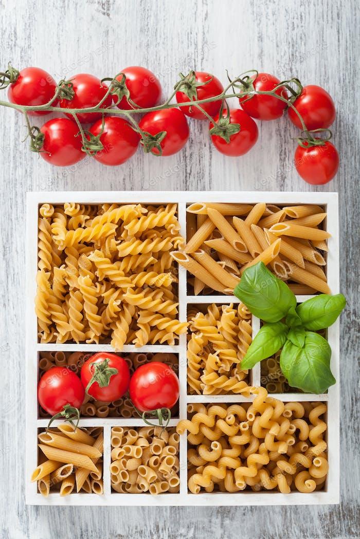 various raw wholegrain pasta in white wooden box