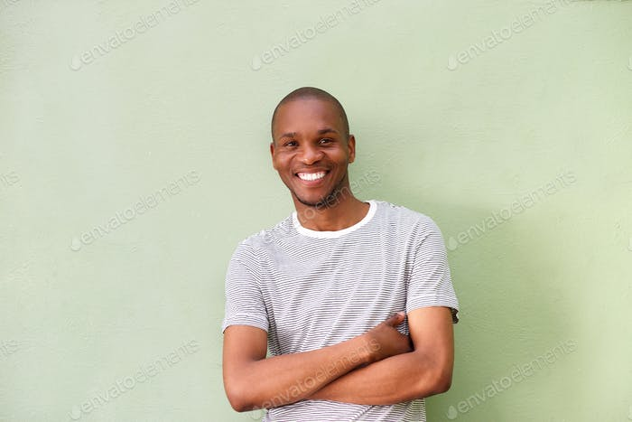 smiling young african man standing against green wall