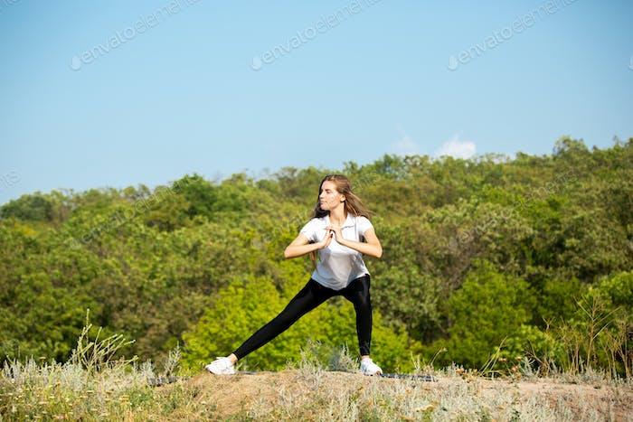 Beautiful young woman training flexibility outdoors