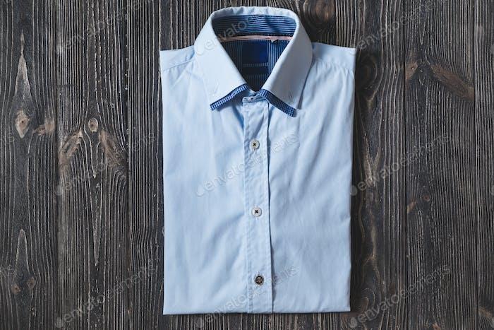 Klassisches blaues Herrenhemd aus Baumwolle mit langen oder kurzen Ärmeln auf schwarzem brutalem Hintergrund.
