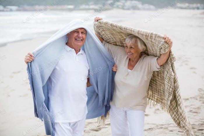 Senior couple holding shawl over head