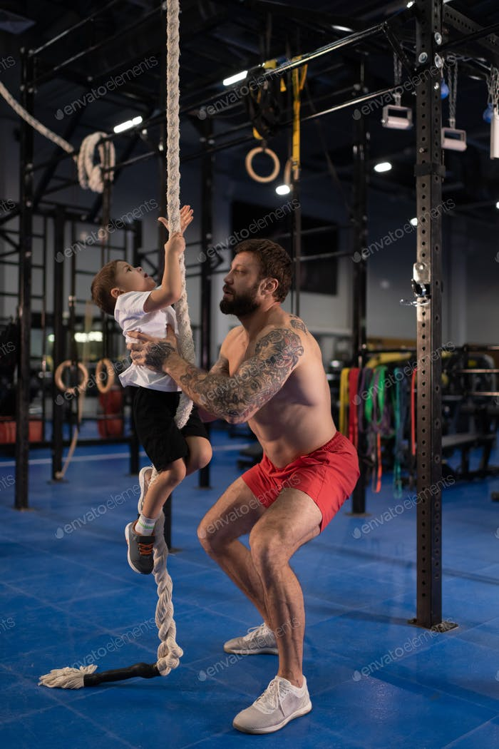 Shirtless father teaching boy to climb rope during training