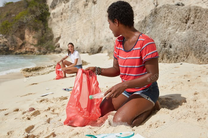 Cleanup day. Outdoor horizontal shot of mixed race young women tidy up beach from wastes, pose on co