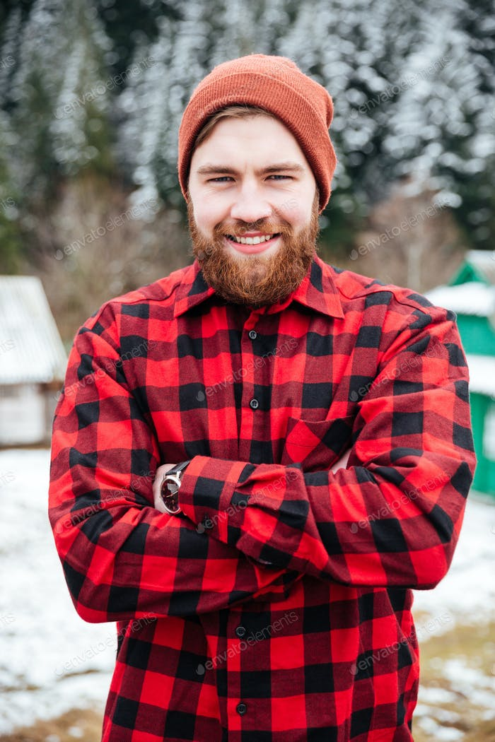 Cheerful bearded man standing with hands folded in winter