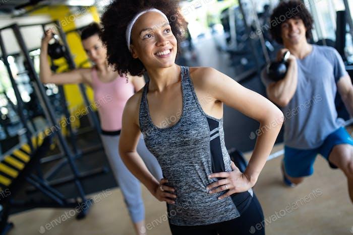 Gruppe von sportlichen Menschen in einem Fitnessstudio Training