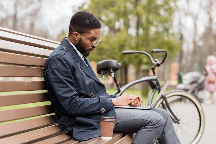 Schöner Manager, der am Laptop im Park arbeitet