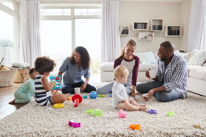 Three friends playing with toddlers on sitting room floor