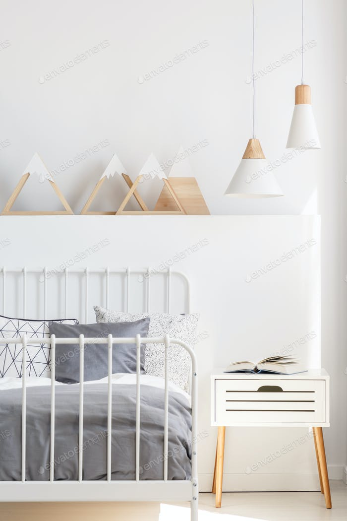 Lamps above bedside cabinet next to bed in white child's bedroom
