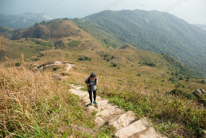 Asian Woman hiking to the top of the mountain