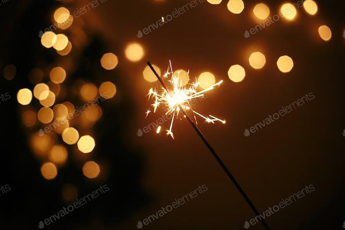 Hand hält glühenden Funker auf dem Hintergrund der goldenen Weihnachtslichter