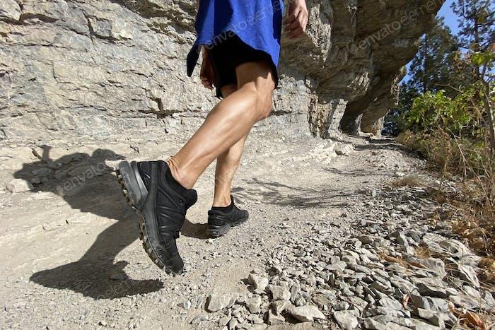 legs man in trekking shoes walking