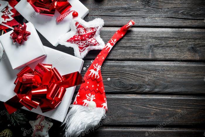 Weiße Geschenkboxen mit Schleifen, Zapfen und Kerzen.