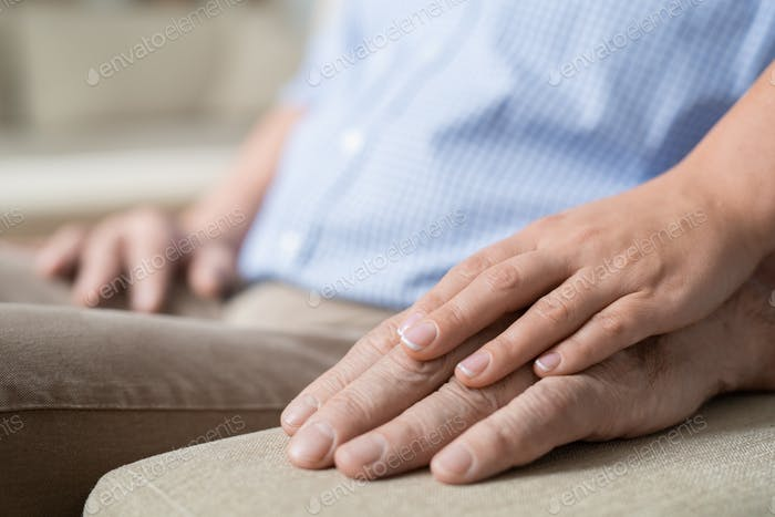Hand of young affectionate and careful woman on that of her senior father