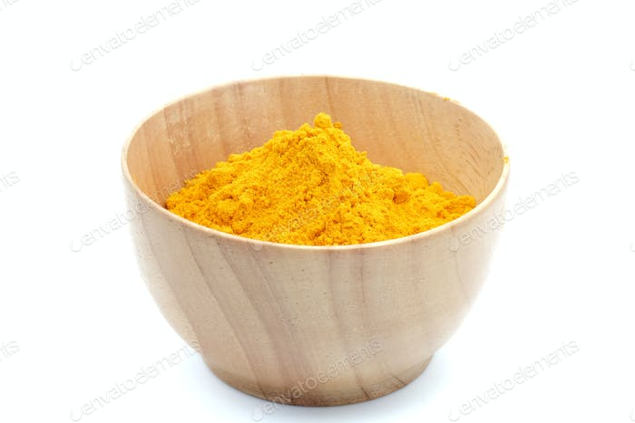 Turmeric powder in woodbowl on white background.