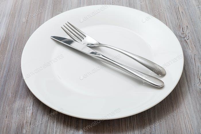 weißer Teller mit Parallelmesser, Löffel auf grau