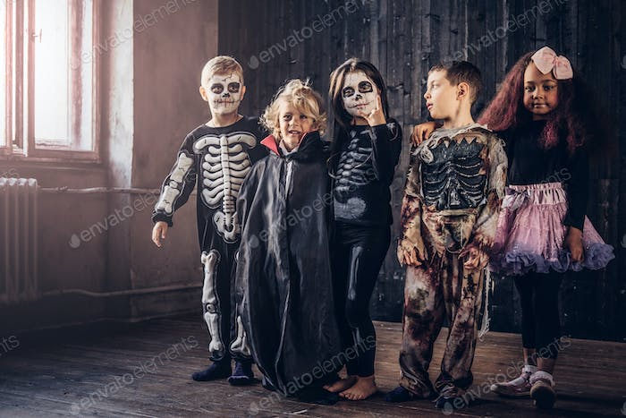 Group of children in costumes during Halloween party in an old house.