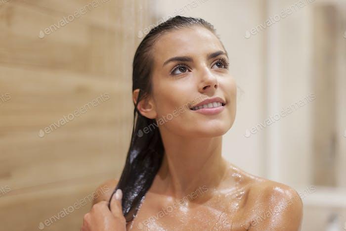 Attractive brunette woman taking shower