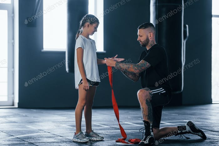 Helping to wear the bandages. Young tattooed boxing coach teaches cute little girl in the gym