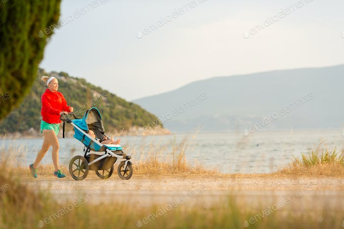 Mother running with stroller, enjoying motherhood at sunset land