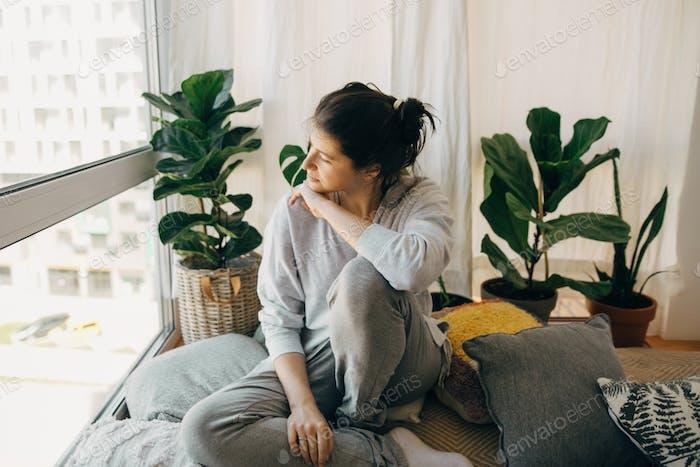 Traurige Hipster Mädchen sitzt zu Hause während der Quarantäne und Blick auf Fenster