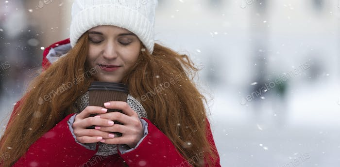Peaceful girl enjoying cup of hot drink on winter day