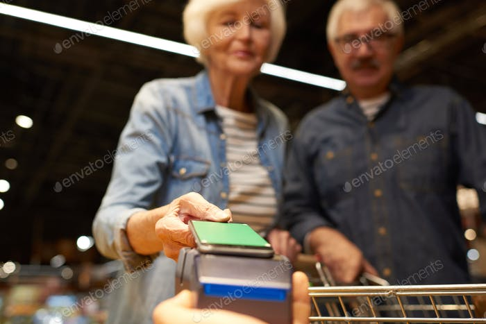 Senior Couple Paying with Smartphone