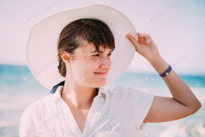 Young Caucasian Lady Woman In Summer Hat Posing Near Sea Beach. Close Up Portrait. Vacation On Sea