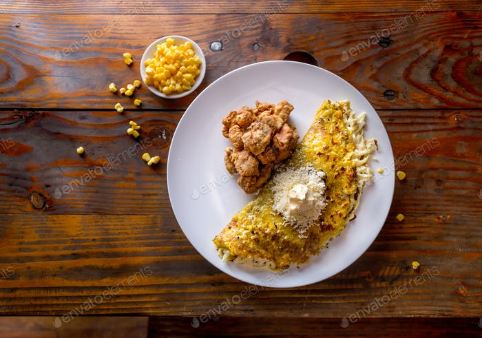 VENEZUELAN FOOD. Corn CACHAPA with cheese and fried pork - cochino frito.
