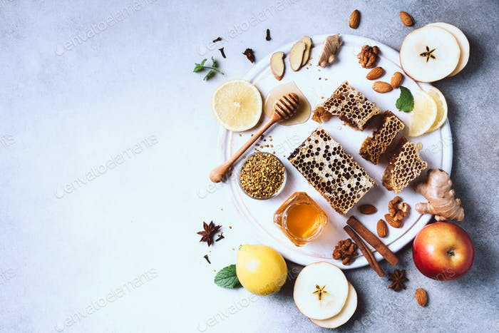 Autumn harvest concept. Set of honey and bee products, apple, lemon, spices on grey concrete
