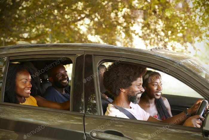 Two black adult couples in a car during a road trip